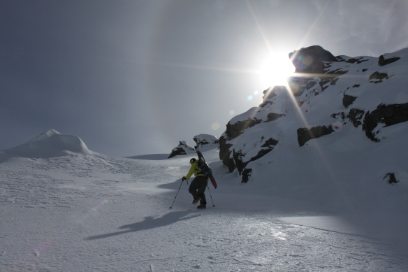 Kyle bootpacks ahead with the sundog high in the sky