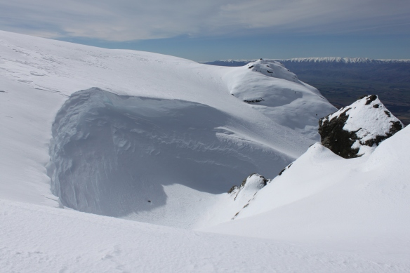 A massive cornice shows the effects the wind has on the snow pack